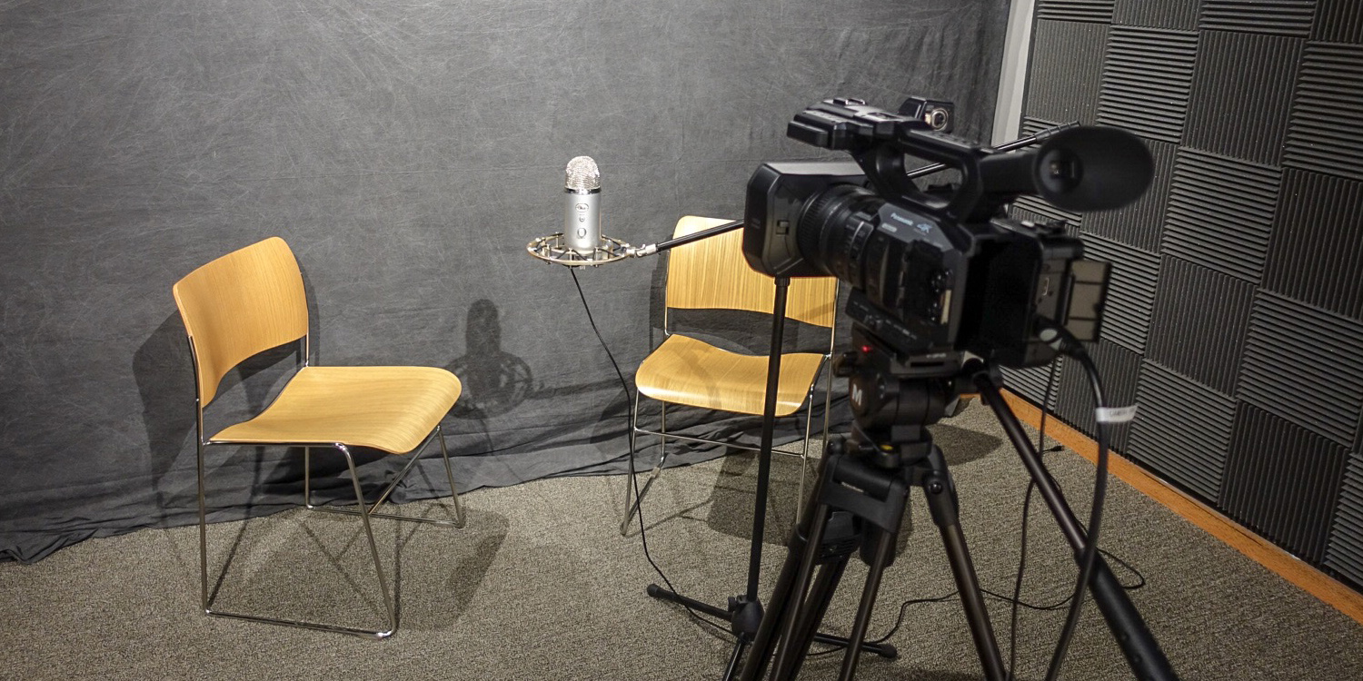 Two chairs, a microphone, and a camera are in the middle of the recording studio.
