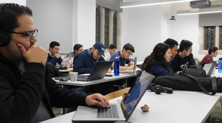 A group of students studying together in Room 121 of the Poorvu Center.