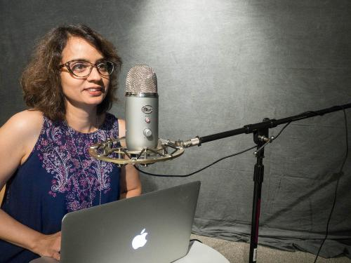 Sanjana Singh sits near a microphone in the CTL studio with her laptop to test the audio.