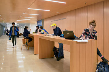 A group of students works at the touchdown desks in the Learning Commons at the Poorvu Center.