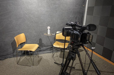 A video camera, a microphone, and two wooden chairs in the CTL recording studio.