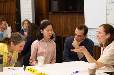 A group of faculty members sit around a table during the SI and discuss a pedagogical topic