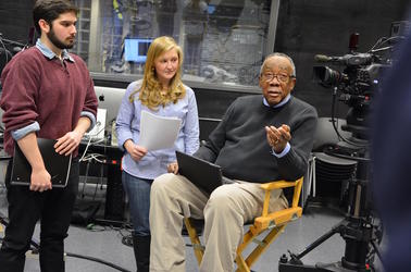 Professor Donald Brown sits with Sara Eperson and a student in the Broadcast Studio