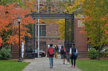 Students walking on Cross Campus near the Memorial Quadrangle Gate during autumn with bright leaves on the trees.