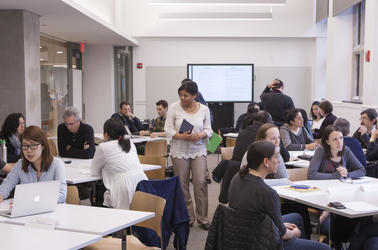 A classroom in the Poorvu Center with faculty working with postdocs