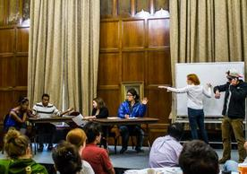 Universityof Michigan CRLT players perform a sketch on a stage in a classroom.