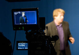 Professor Bloom stands behind a television camera in the Yale Broadcast Studio