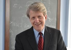 Professor Robert Shiller, wearing a suit with a red tie and blue shirt, stands in front of a black board.
