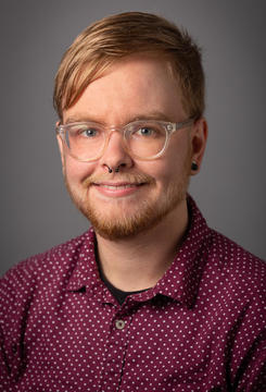 A white nonbinary person with short blonde hair and a maroon polka-dotted collared shirt smiles in front of a grey background. They have clear-framed round glasses, a septum piercing, and gauged ears.