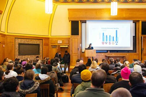 A view of Linsly-Chittenden Hall Room 102 with students and Yale community members seated facing a screen with a PowerPoint slide and a person standing at the podium
