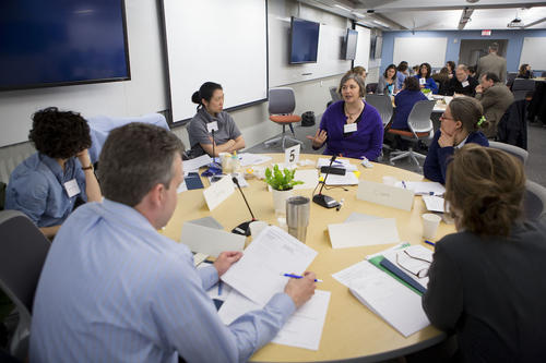 A group of Faculty Members discuss pedagogy during the Summer Institute on Course Redesign at a round table in the TEAL classroom.